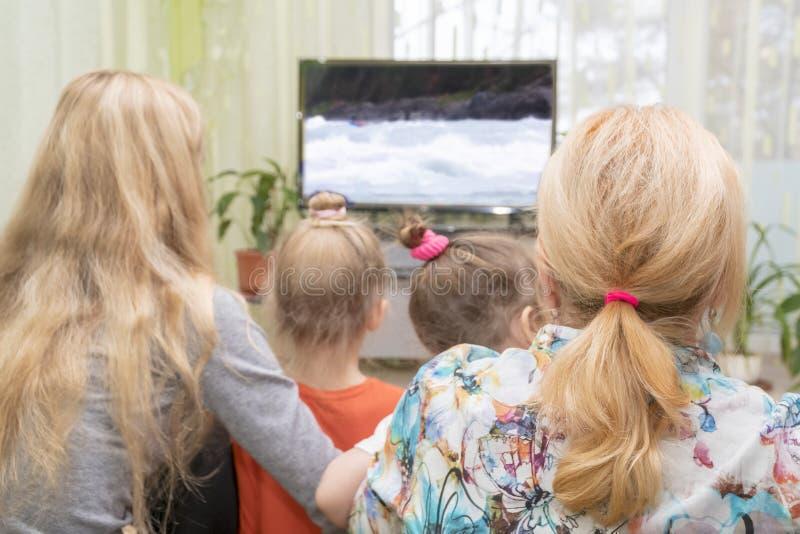 家庭看着电视,背面图 库存照片