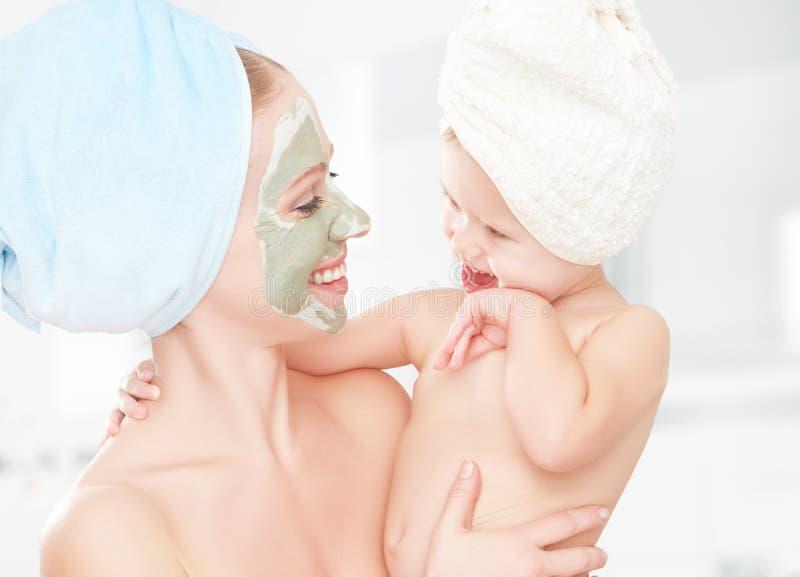 家庭秀丽治疗在卫生间里 母亲和女儿女婴做面孔皮肤的一个面具 库存图片