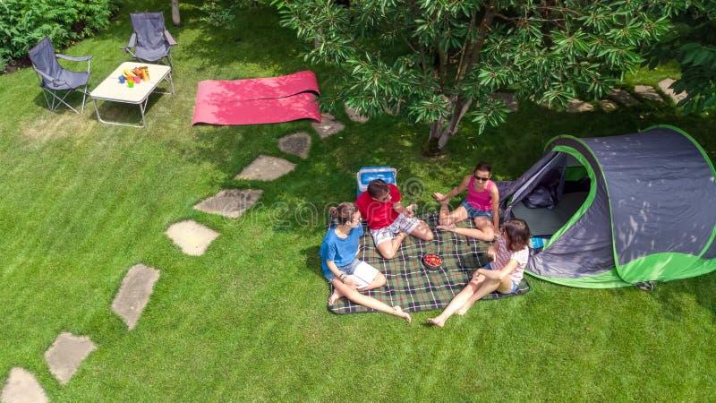 家庭空中顶视图在从上面露营地,父母和孩子在公园、帐篷和野营的设备放松并且获得乐趣 库存图片