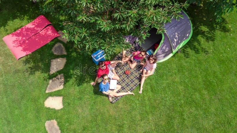 家庭空中顶视图在从上面露营地,父母和孩子在公园、帐篷和野营的设备放松并且获得乐趣 免版税图库摄影