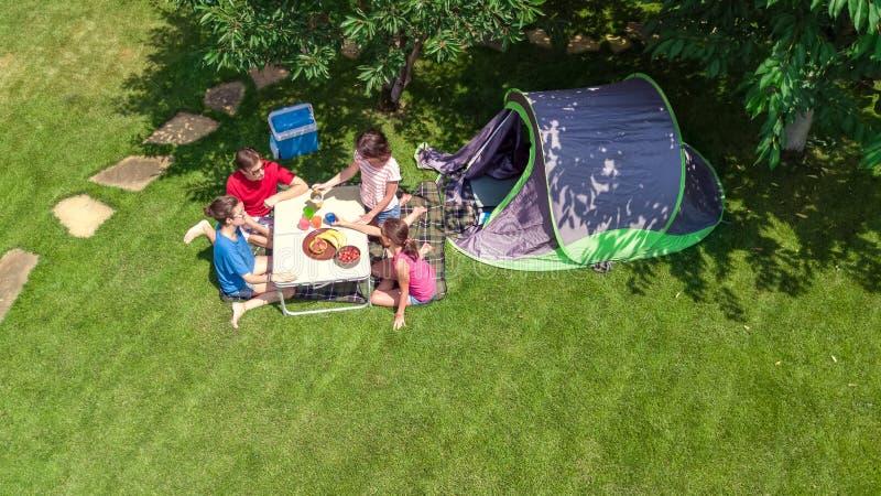 家庭空中顶视图在从上面露营地,父母和孩子在公园、帐篷和野营的设备放松并且获得乐趣 免版税库存照片