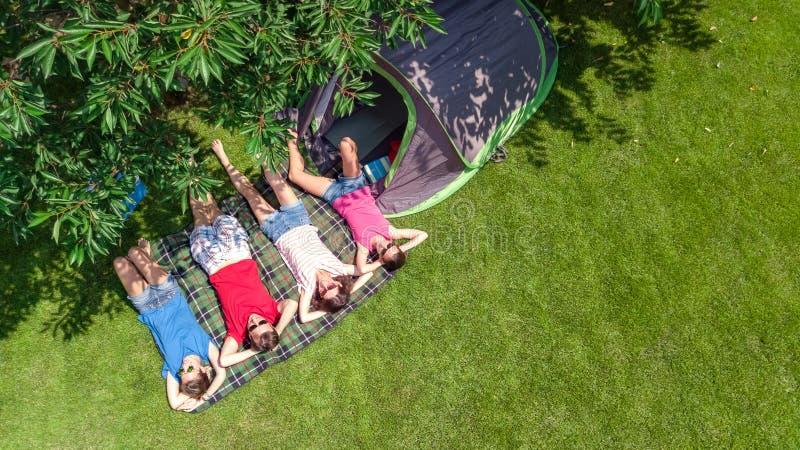 家庭空中顶视图在从上面露营地,父母和孩子在公园、帐篷和野营的设备放松并且获得乐趣 库存照片
