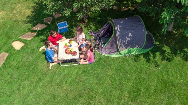 家庭空中顶视图在从上面露营地,父母和孩子在公园、帐篷和野营的设备放松并且获得乐趣 免版税库存图片