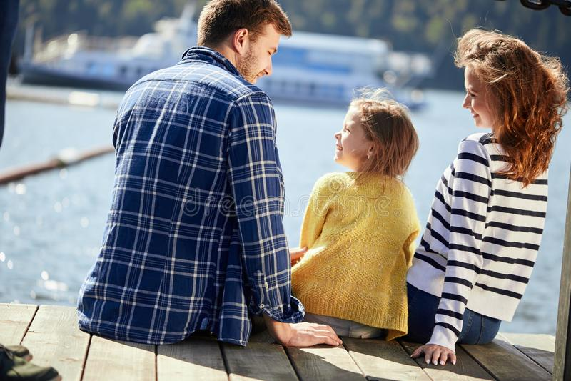 家庭背面图坐码头在秋天天 秋天家庭画象 免版税图库摄影