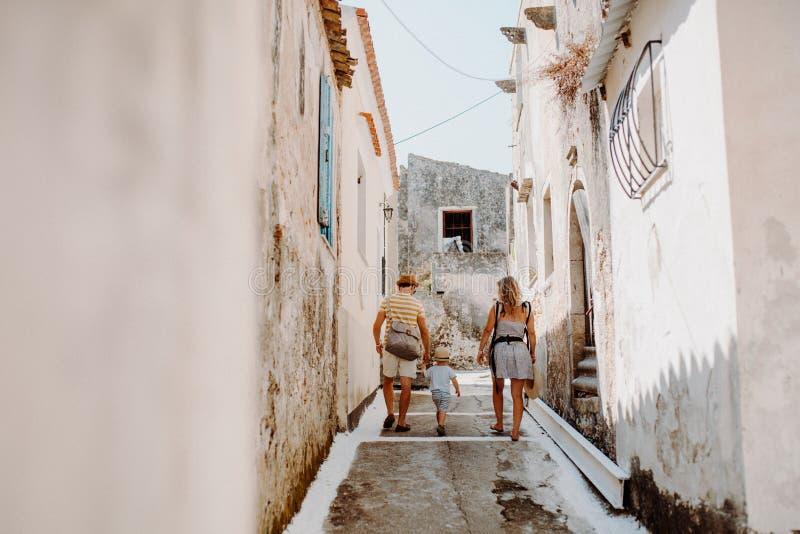 家庭背面图有走在海滩的两个小孩孩子的在度假夏天休假 库存照片
