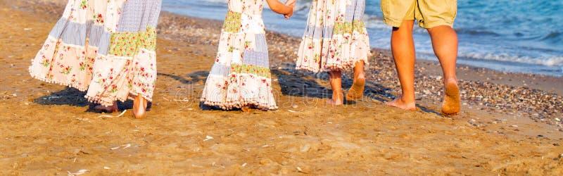 家庭脚和腿在沙子靠岸 库存图片