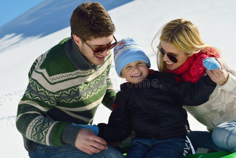 家庭获得在新鲜的雪的乐趣冬天假期 免版税库存照片