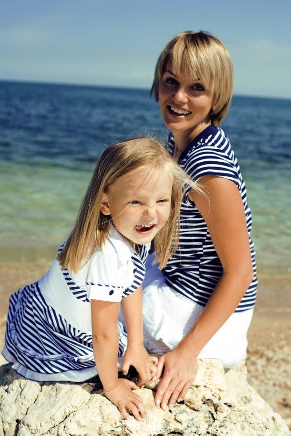 家庭获得在海滩、母亲和女儿的乐趣海上 库存图片