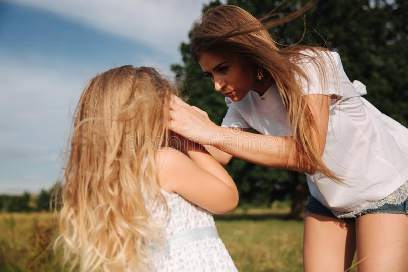 家庭获得在近的大树之外的乐趣 虽则母亲和女儿步行草 库存图片