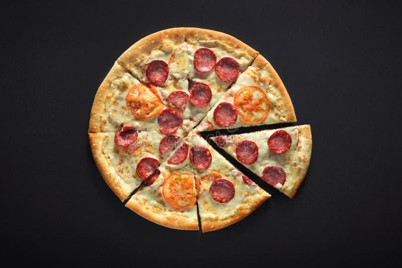 家庭薄饼用意大利辣味香肠,蕃茄,碳酸盐,在黑石背景的无盐干酪 免版税库存照片