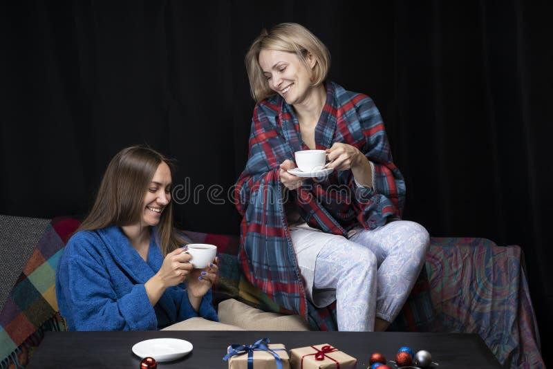 家庭衣裳的妇女喝茶 黑色背景 库存图片