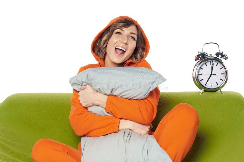 家庭衣裳的妇女坐拥抱枕头的沙发 图库摄影