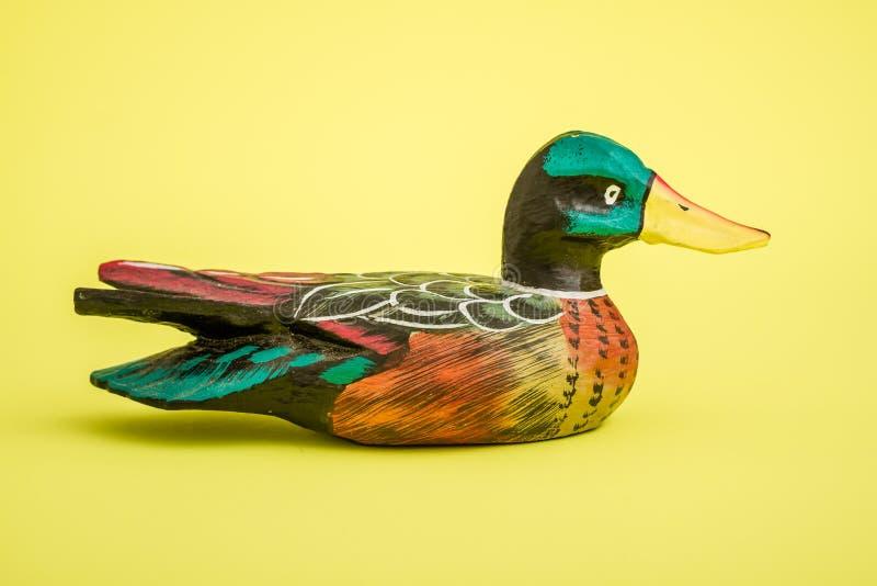家庭装饰的手工制造木鸭子在黄色背景 库存图片