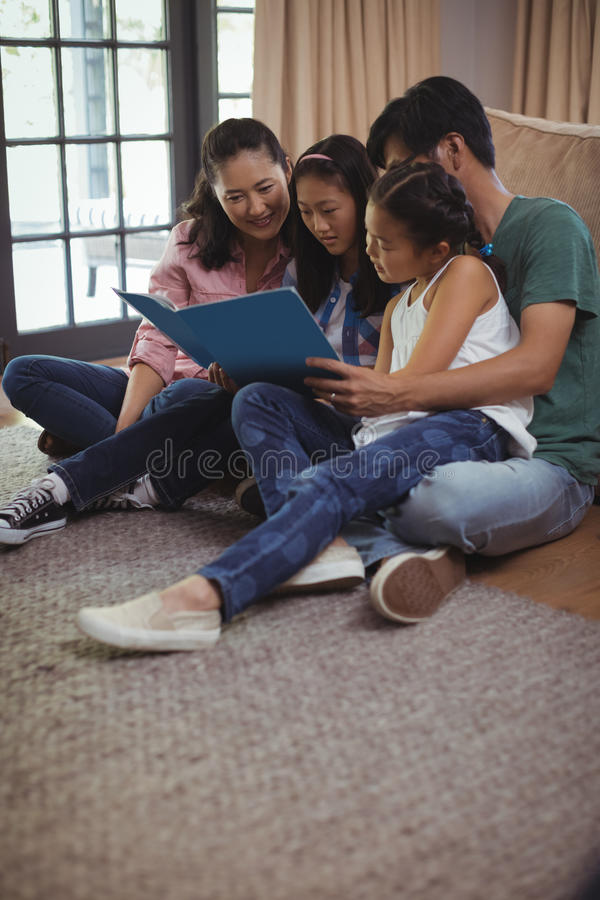 家庭观看的象册一起在客厅 免版税图库摄影