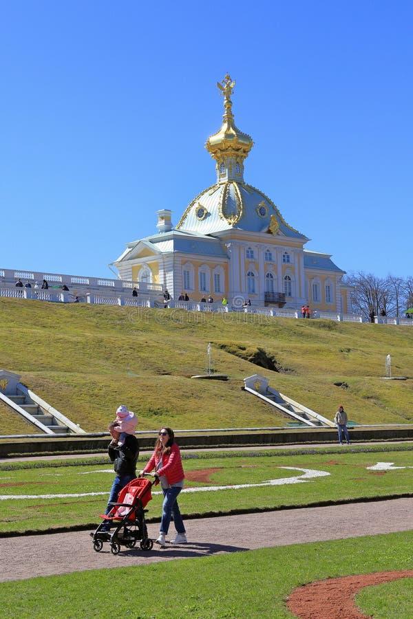 家庭走与在Peterhof的吸引力的中一个孩子在圣彼德堡 库存图片