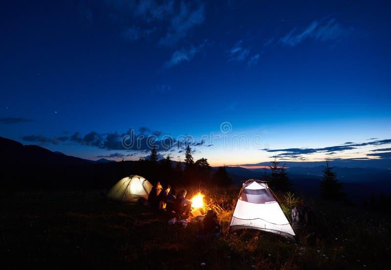 家庭远足者有休息在野营的晚上在山 免版税图库摄影
