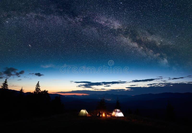家庭远足者有休息在野营的晚上在山 免版税库存图片