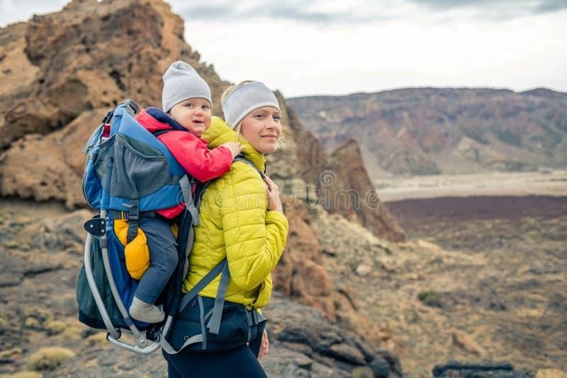 家庭远足,有婴孩的母亲背包的 库存照片