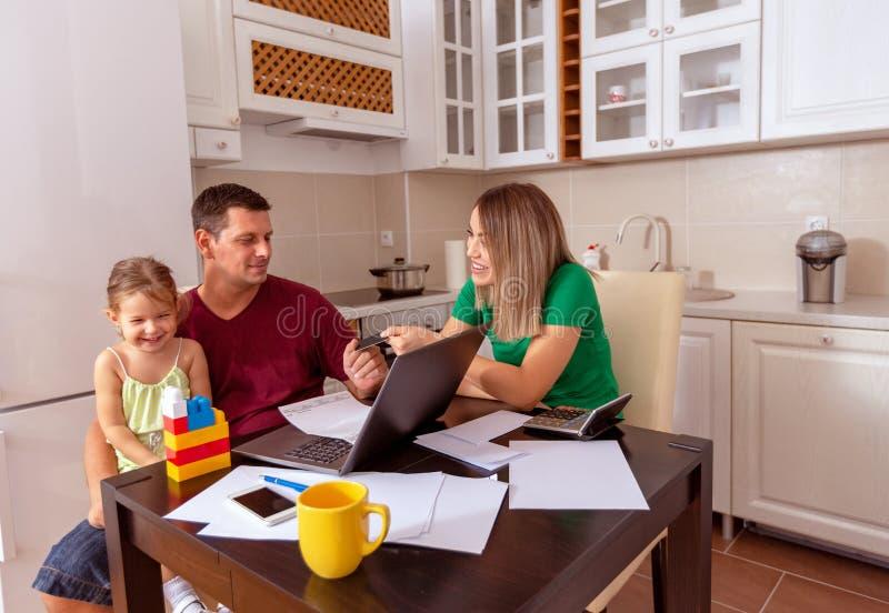 家庭-母亲、父亲和女儿满意和美丽对微笑在家一起在有膝上型计算机购物的厨房里 库存照片
