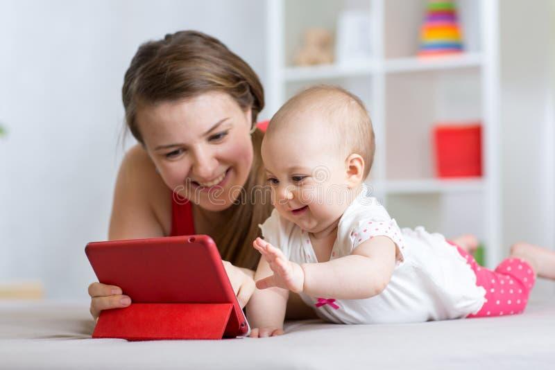 家庭-母亲和婴孩有片剂的在地板上在家 放松在片剂计算机的妇女和儿童女孩 免版税图库摄影