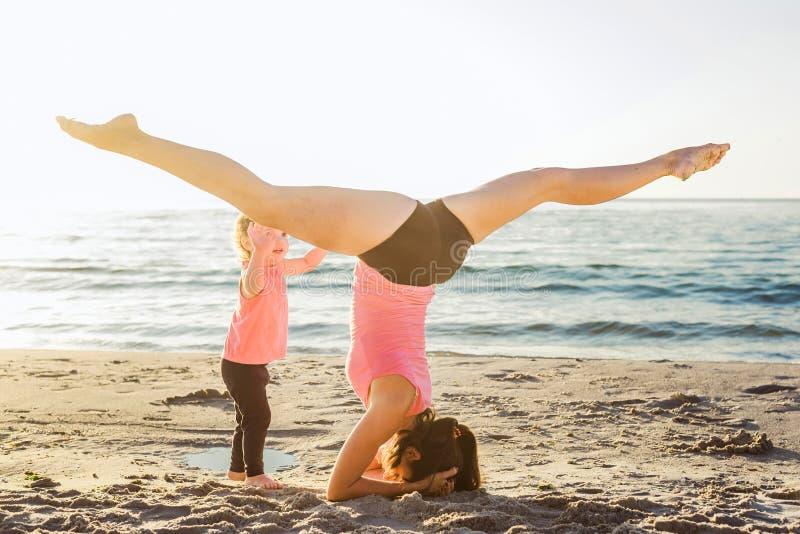 家庭锻炼-做在海滩的母亲和女儿锻炼 图库摄影