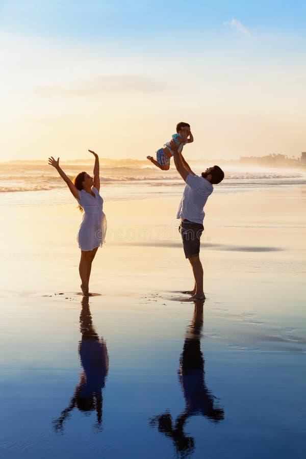 家庭-父亲,母亲,在日落海滩的婴孩步行 免版税图库摄影