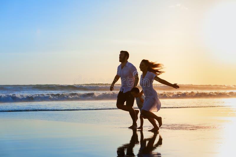 家庭-父亲,母亲,在日落海滩跑的婴孩 免版税库存照片