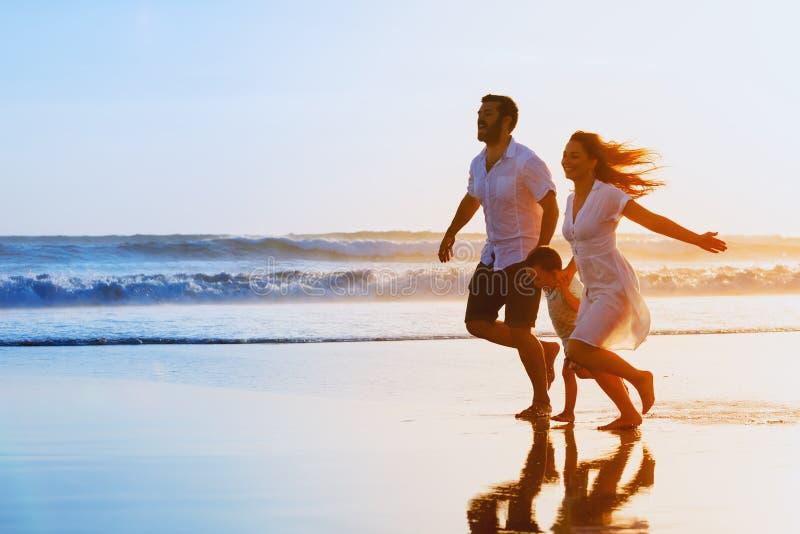 家庭-父亲,母亲,在日落海滩跑的婴孩 免版税库存图片