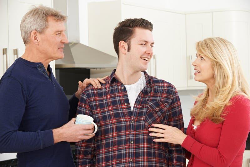 家庭画象与成人儿子的在家 免版税库存照片
