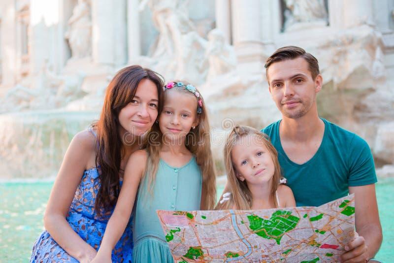 家庭画象与旅游地图的在Fontana di Trevi,罗马,意大利附近 愉快的父母和孩子享受意大利假期 图库摄影