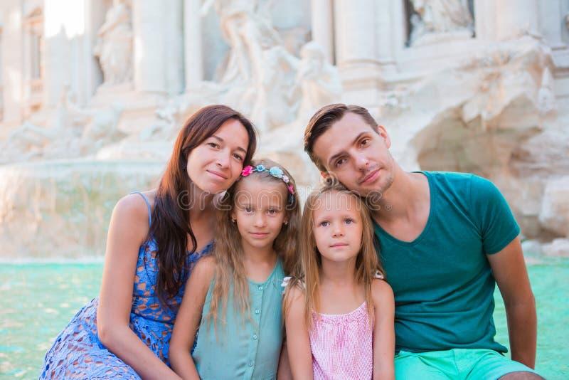 家庭画象在Fontana di Trevi,罗马,意大利 愉快的父母和孩子在欧洲享受意大利假期假日 免版税库存图片