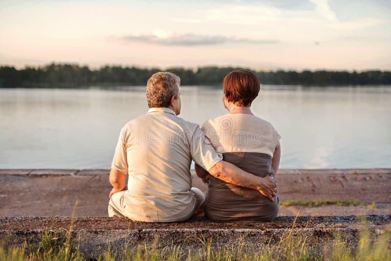 家庭年长夫妇坐观看日落的湖和河的岸 免版税库存图片