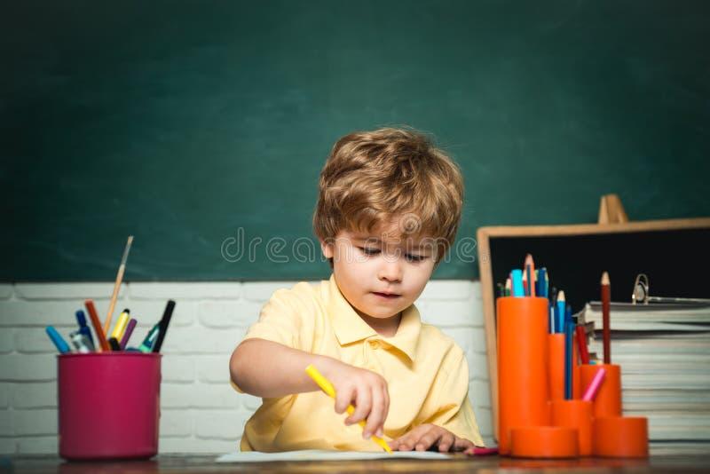 家或学校教育 从小学的画象孩子 E 与书的愉快的逗人喜爱的聪明的男孩学生 免版税库存图片