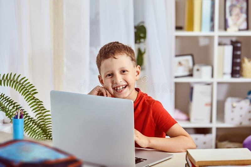 家教,查寻和研究,新知识 愉快的孩子在与计算机的桌上 坐在桌上的小男孩学生 免版税库存图片