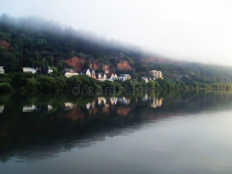 家行在与有薄雾的天空的河水反射 库存照片