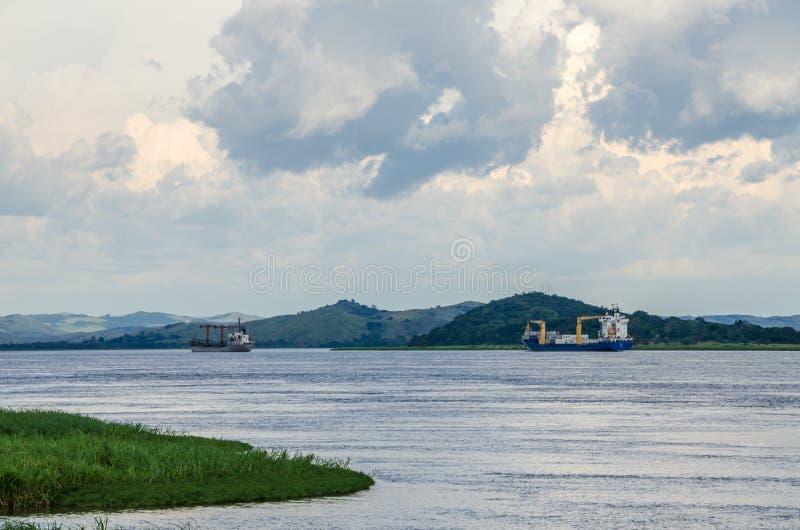 容器在强大刚果河的货船有剧烈的多云天空和豪华的绿草的在前景, DRC,非洲 库存照片