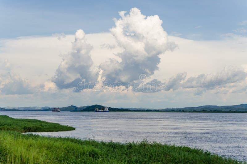 容器在强大刚果河的货船有剧烈的天空的 免版税库存照片