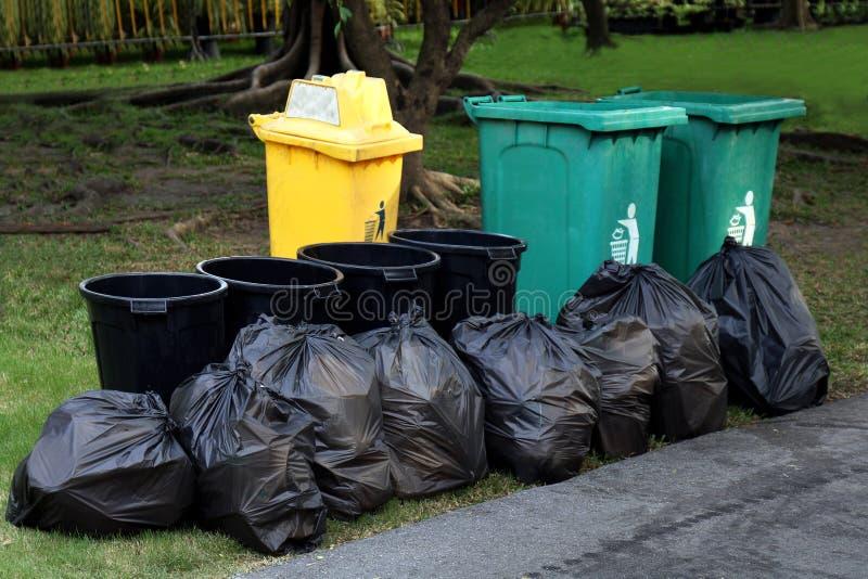 容器废塑料、垃圾在黑袋子和容器,堆容器垃圾破烂物土和垃圾袋许多在庭院公园,回收 免版税库存照片