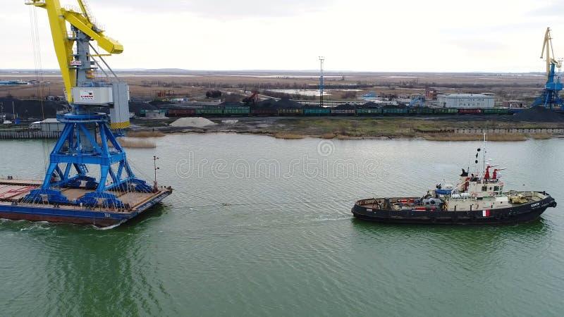 容器的拖曳起重机 拖轮拉扯的大集装箱船 下来上面鸟瞰图 容器货物货物 库存照片