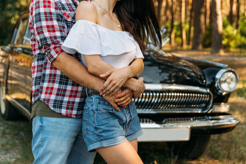 容忍 爱和喜爱在一对年轻夫妇之间在公园,在老汽车附近 格子花呢披肩飞机和牛仔裤的,一个女孩一个人简而言之 库存照片