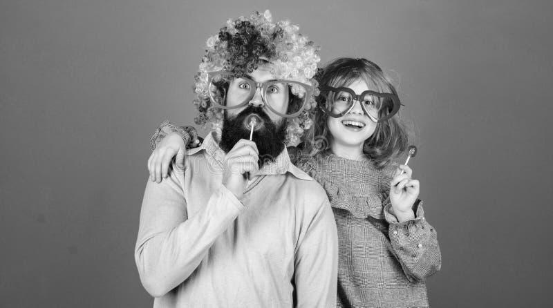 容易的单一方式是乐趣嬉戏的父母 人有胡子的父亲和女孩穿戴五颜六色的假发,当吃棒棒糖糖果时 事情 库存图片