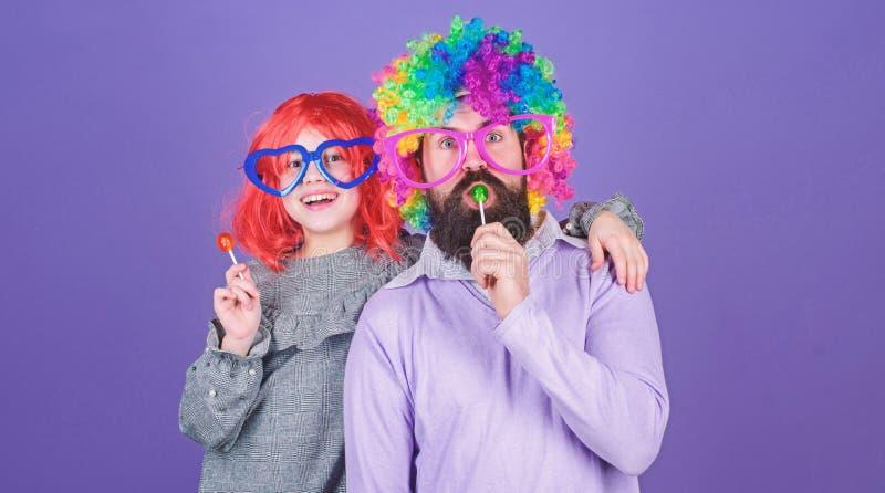 容易的单一方式是乐趣嬉戏的父母 人有胡子的父亲和女孩穿戴五颜六色的假发,当吃棒棒糖糖果时 ?? 库存图片