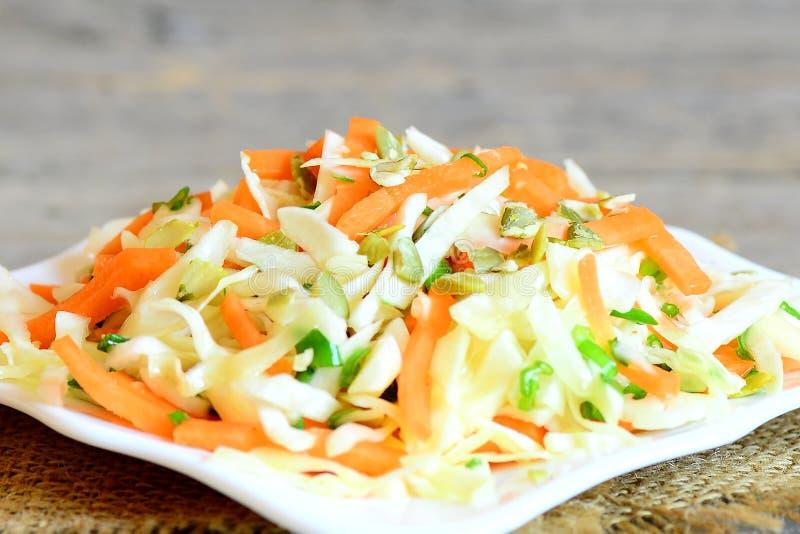 容易的自创凉拌卷心菜沙拉 鲜美凉拌卷心菜沙拉用红萝卜、葱和南瓜籽在板材和在一张木桌上 库存图片