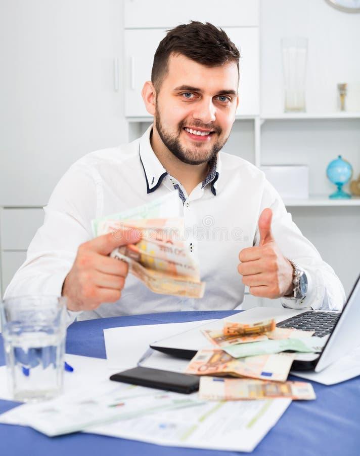 容易年轻男性商人收入金钱在网上在互联网 免版税库存照片