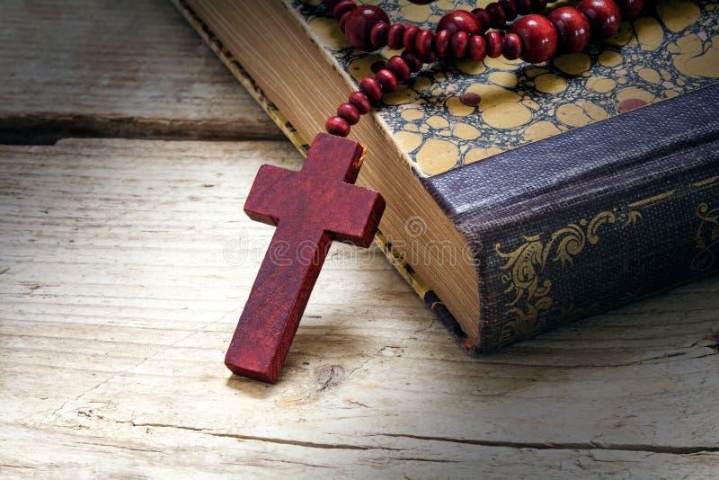 宽容木念珠成串珠状与在一本旧书的十字架在土气 免版税库存照片