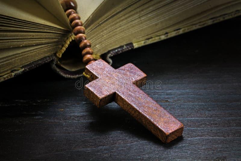 宽容木念珠成串珠状与在一本旧书的十字架在黑暗的r 免版税库存照片