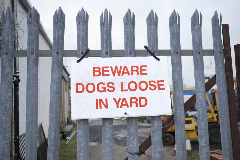 宽松当心狗在金属栏杆的围场标志安全的 库存图片