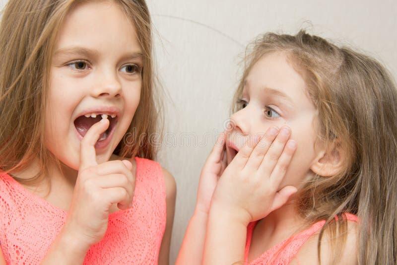 宽松显示她的姐妹乳齿的六年女孩 免版税库存照片