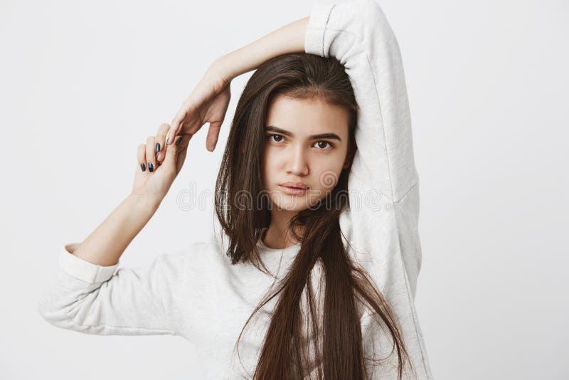 宽松留着黑暗的长的头发的美丽的十几岁的女孩,摆在户内,穿戴了随便,看与呼吁照相机 免版税图库摄影