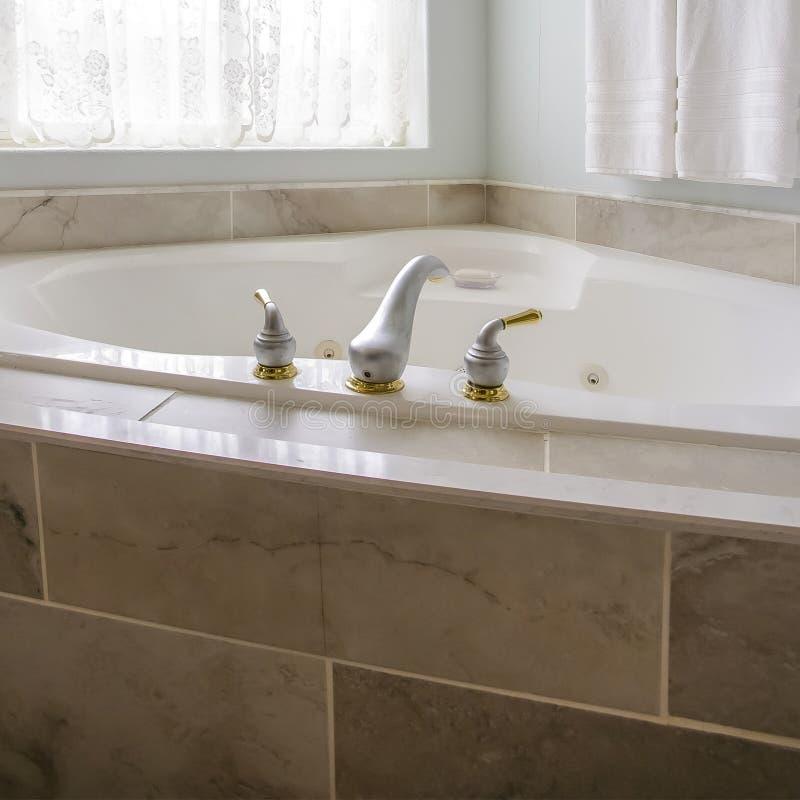 宽阔在浴缸在一个卫生间的角落有一个大被成拱形的窗口的 图库摄影